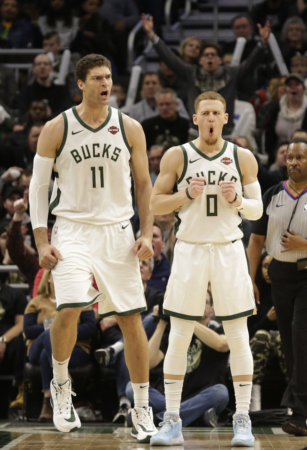 Milwaukee Bucks' Brook Lopez (11) and Donte DiVincenzo react to a foul called on Lopez during the second half of an NBA basketball game against the Mi...