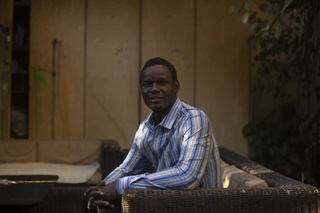 """In this Nov. 27, 2019 photo, Patrice Gaudensio, a refugee artist from South Sudan poses for a portrait during an exhibition titled """"Beyond Borders,"""" f..."""
