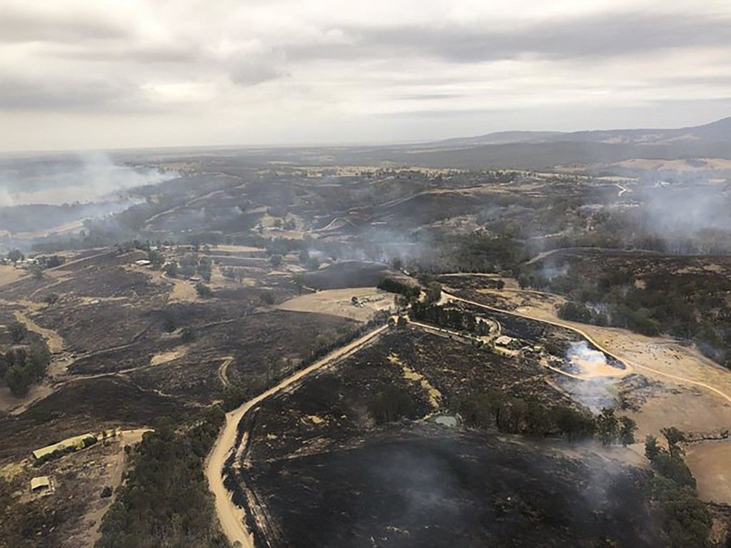 In this Monday, Dec. 30, 2019, aerial photo, acres of scorched land are seen in Bairnsdale, Australia. Thousands of tourists fled Australia's wildfire...
