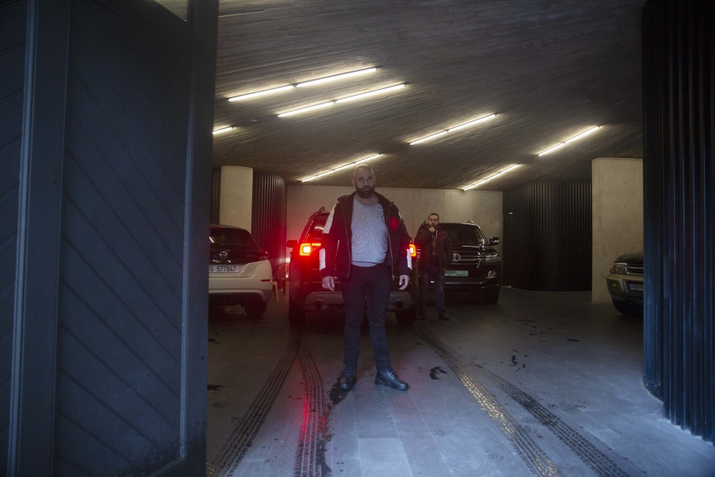 Men stand guard next to a vehicle as it arrives in the car park at the home of former Nissan Chairman Carlos Ghosn in Beirut, Lebanon, Thursday, Jan. ...