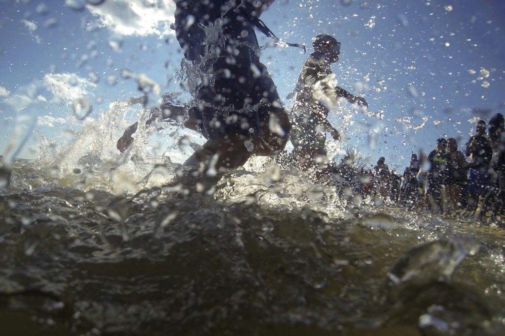 People run into the Chesapeake Bay while dipping in the frigid waters as part of a polar bear plunge New Year event, Wednesday, Jan. 1, 2020, in North...