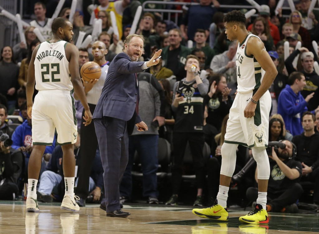 Milwaukee Bucks coach Mike Budenholzer, center, talks to his players during the second half of the team's NBA basketball game against the Minnesota Ti...