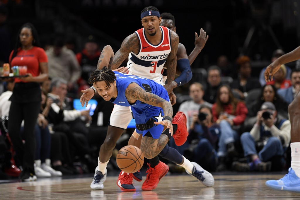 Orlando Magic guard Markelle Fultz, front, chases a loose ball in front of Washington Wizards guard Bradley Beal (3) during the first half of an NBA b...