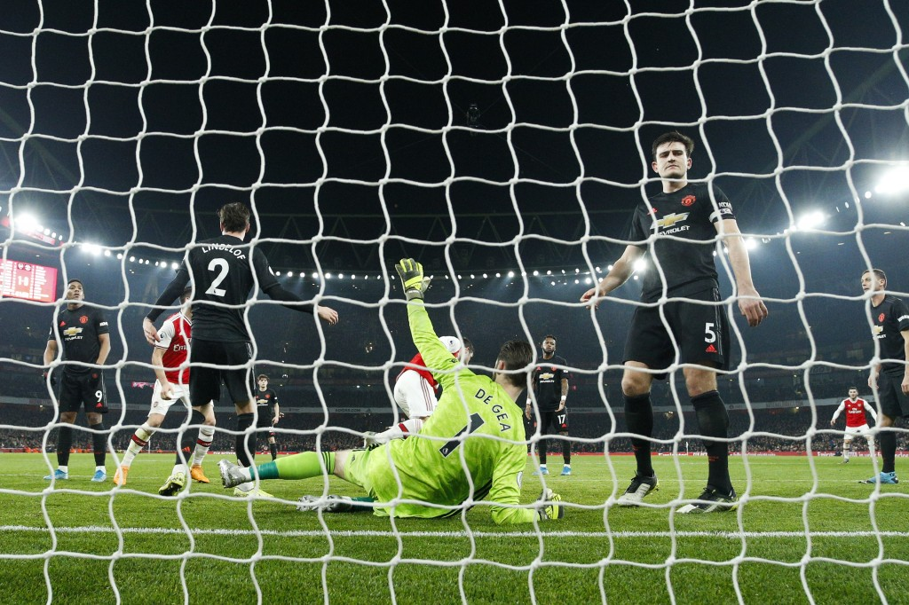 Manchester United goalkeeper David de Gea, center, lies on the ground after being beaten by Arsenal's Sokratis Papastathopoulos during the English Pre...