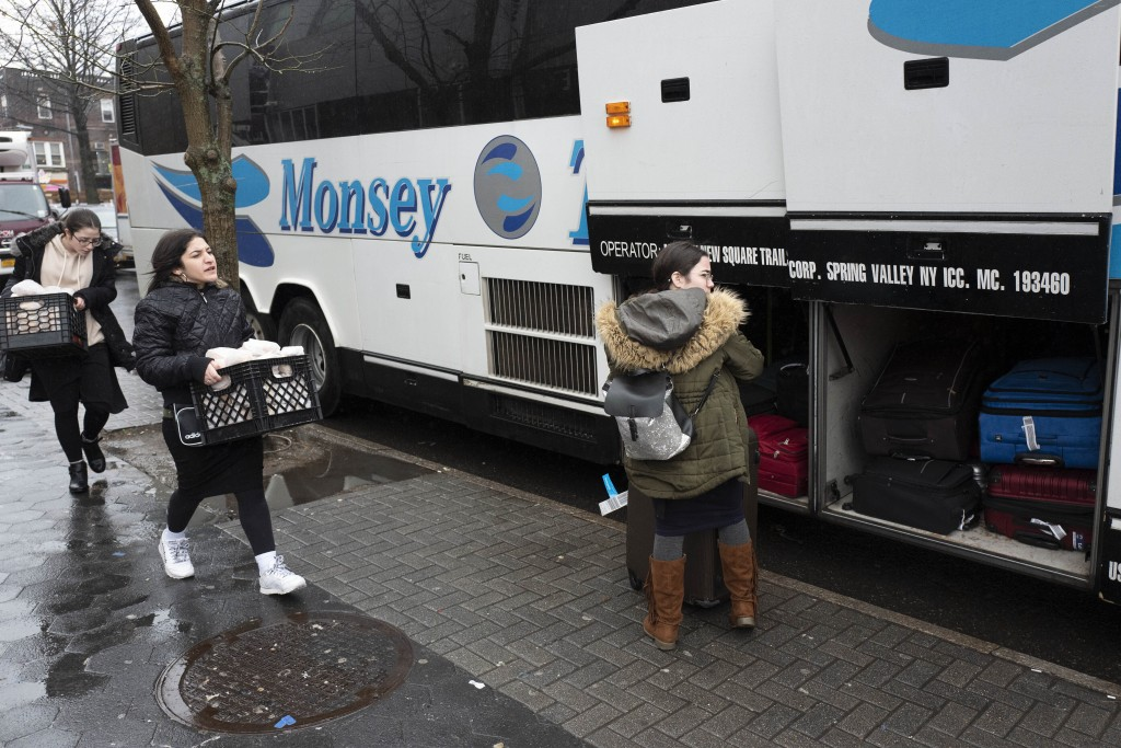 In this Dec. 30, 2019, photo, Jewish girls walk to a bus in the Crown Heights neighborhood of New York, for the trip to Monsey, N.Y. Monsey Trails com...