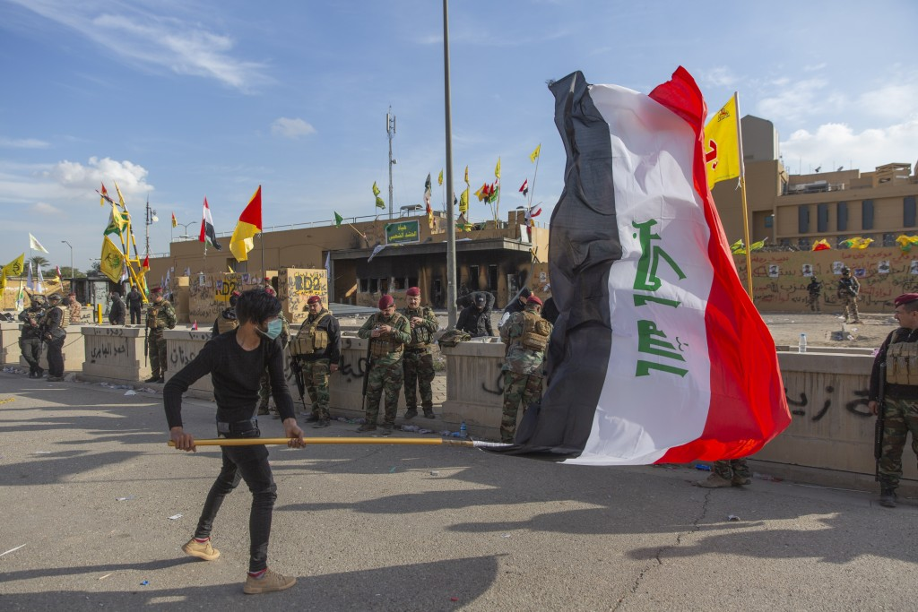 A man waves the Iraqi flag while the Iraqi army soldiers are deployed in front of the U.S. embassy, in Baghdad, Iraq, Wednesday, Jan. 1, 2020. Iran-ba...