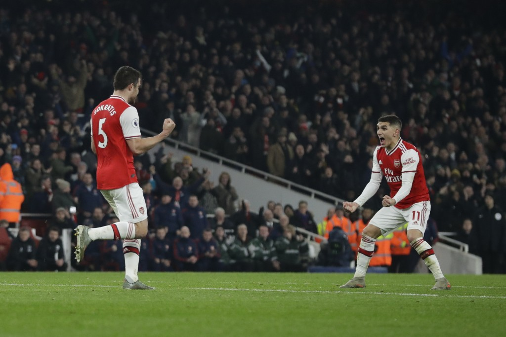 Arsenal's Sokratis Papastathopoulos, left, celebrates with teammate Lucas Torreira after scoring their side's second goal during the English Premier L...