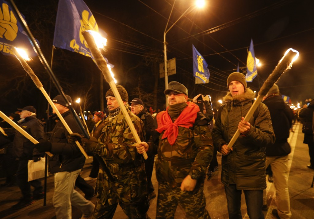 Activists of various nationalist parties carry torches during a rally in Kyiv, Ukraine, Wednesday, Jan. 1, 2020. The rally was organized to mark the b...