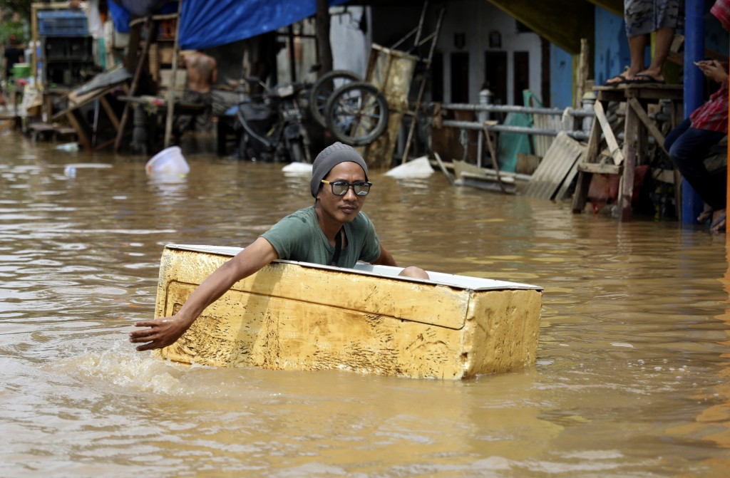 A man rides floats in a styrofoam box on a flooded street in Jakarta, Indonesia, Thursday, Jan. 2, 2020. Severe flooding in the capital as residents c...