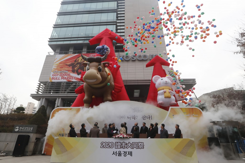 South Korean financial officers celebrate the opening of this year's trading in Seoul, South Korea, Thursday, Jan. 2, 2020. Asian shares were mostly h...