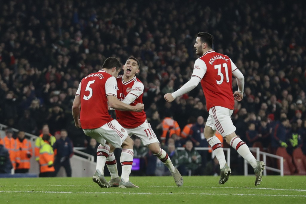Arsenal's Sokratis Papastathopoulos, left, celebrates with teammate Lucas Torreira and Sead Kolasinac, right, after scoring their side's second goal d...