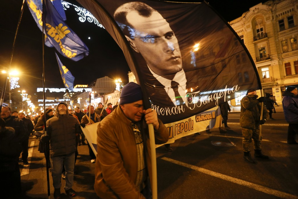 Activists of various nationalist parties carry torches and a portrait of Stepan Bandera during a rally in Kyiv, Ukraine, Wednesday, Jan. 1, 2020. The ...