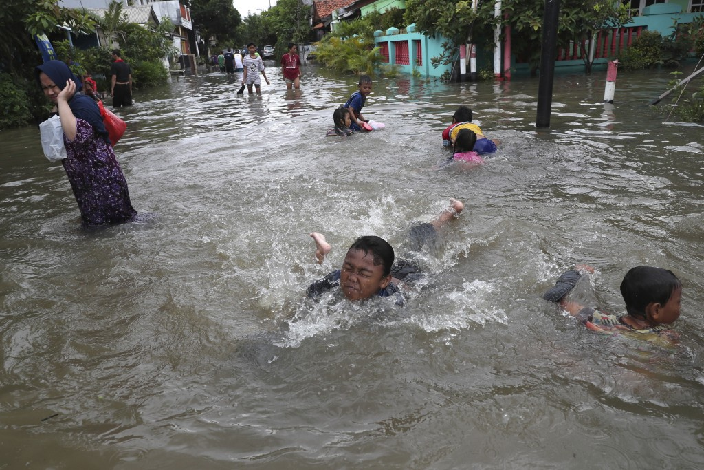 Children play in a flooded neighborhood in Tanggerang on the outskirts of Jakarta, Indonesia, Thursday, Jan. 2, 2020. Severe flooding in Indonesia's c...