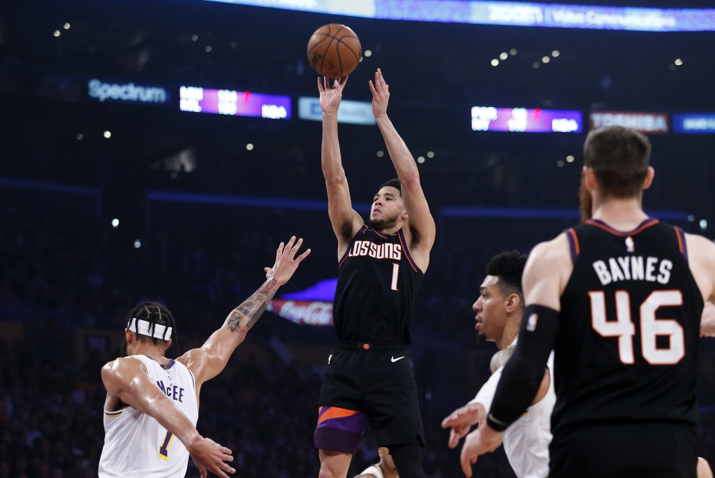 Phoenix Suns' Devin Booker (1) shoots next to Los Angeles Lakers' JaVale McGee (7) during the first half of an NBA basketball game Wednesday, Jan. 1, ...
