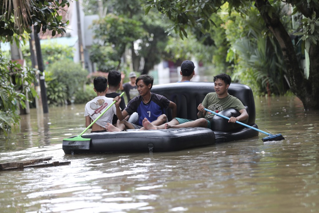 Residents use an inflatable chair as a raft to make their way through a flooded neighborhood in Tanggerang on the outskirts of Jakarta, Indonesia, Thu...