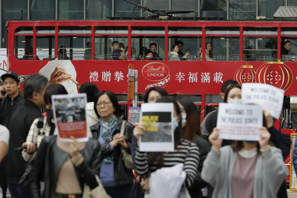 Residents watch from a tram as protesters rally in Hong Kong  Thursday, Jan. 2, 2020. Hundreds of thousands of people packed Hong Kong streets for an ...