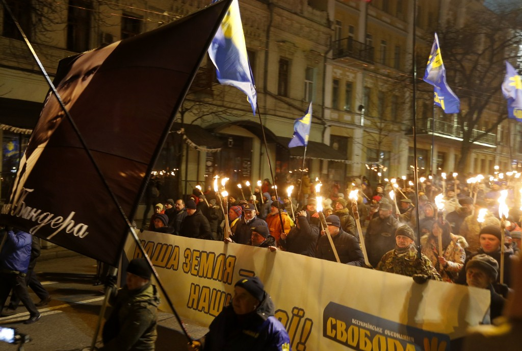 Activists of various nationalist parties carry torches, portrait of Stepan Bandera and banner reads 'Our land - our heroes' during a rally in Kyiv, Uk...