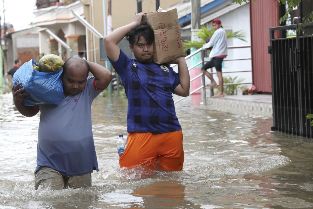 Residents wade through a flooded neighborhood in Tanggerang on the outskirts of Jakarta, Indonesia, Thursday, Jan. 2, 2020. Heavy flooding in Indonesi...