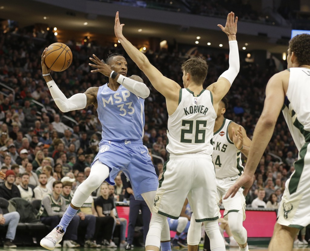 Minnesota Timberwolves' Robert Covington (33) passes the ball during the first half of the team's NBA basketball game against the Milwaukee Bucks on W...