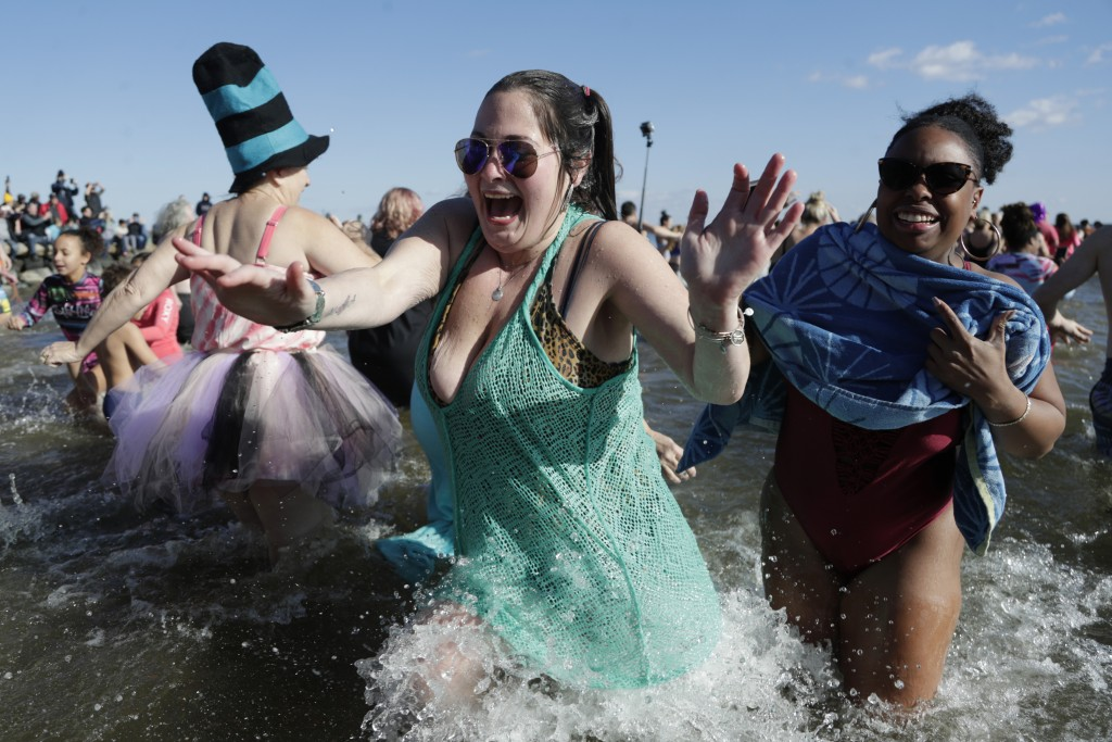 A woman reacts as she hurries out of the Chesapeake Bay after dipping himself in the frigid waters as part of a polar bear plunge New Year event, Wedn...