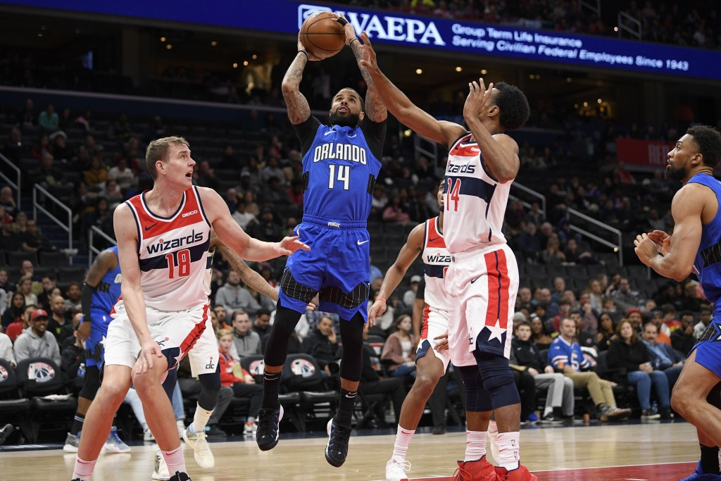 Orlando Magic guard D.J. Augustin (14) goes to the basket between Washington Wizards center Anzejs Pasecniks (18) and guard Ish Smith (14) during the ...