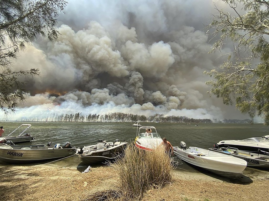 Boats are pulled ashore as smoke and wildfires rage behind Lake Conjola, Australia, Thursday, Jan. 2, 2020. Thousands of tourists fled Australia's wil...