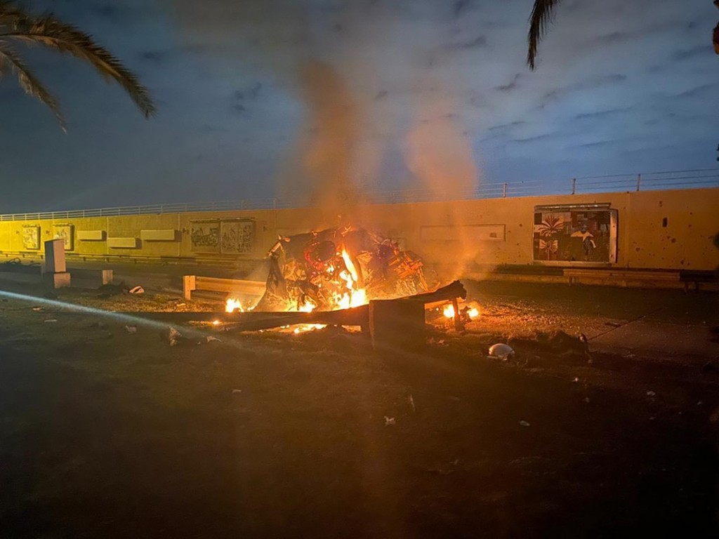 This photo released by the Iraqi Prime Minister Press Office shows a burning vehicle at the Baghdad International Airport following an airstrike in Ba...
