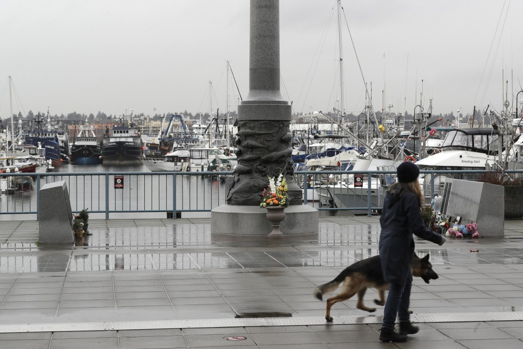 A pedestrian and a dog walk past the Seattle Fishermen's Memorial, Thursday, Jan. 2, 2020, in Seattle. Items left at the memorial Thursday included a ...