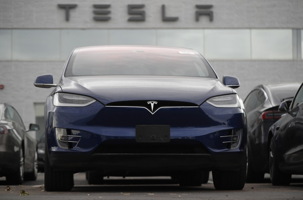 In this Oct. 20, 2019, photo an unsold 2019 Model X sits under a sign at a Tesla dealership in Littleton, Colo.  Tesla says its global deliveries rose...