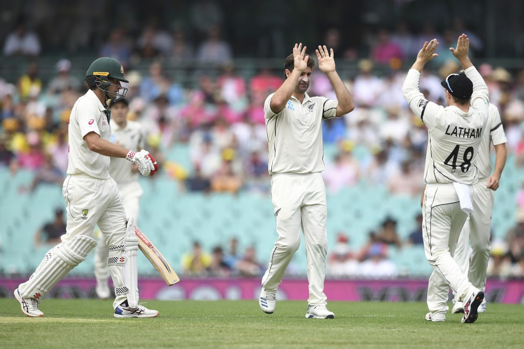 New Zealand bowler Colin de Grandhomme, center, celebrates the wicket of Burns with Tom Latham on day one of the third cricket test match between Aust...