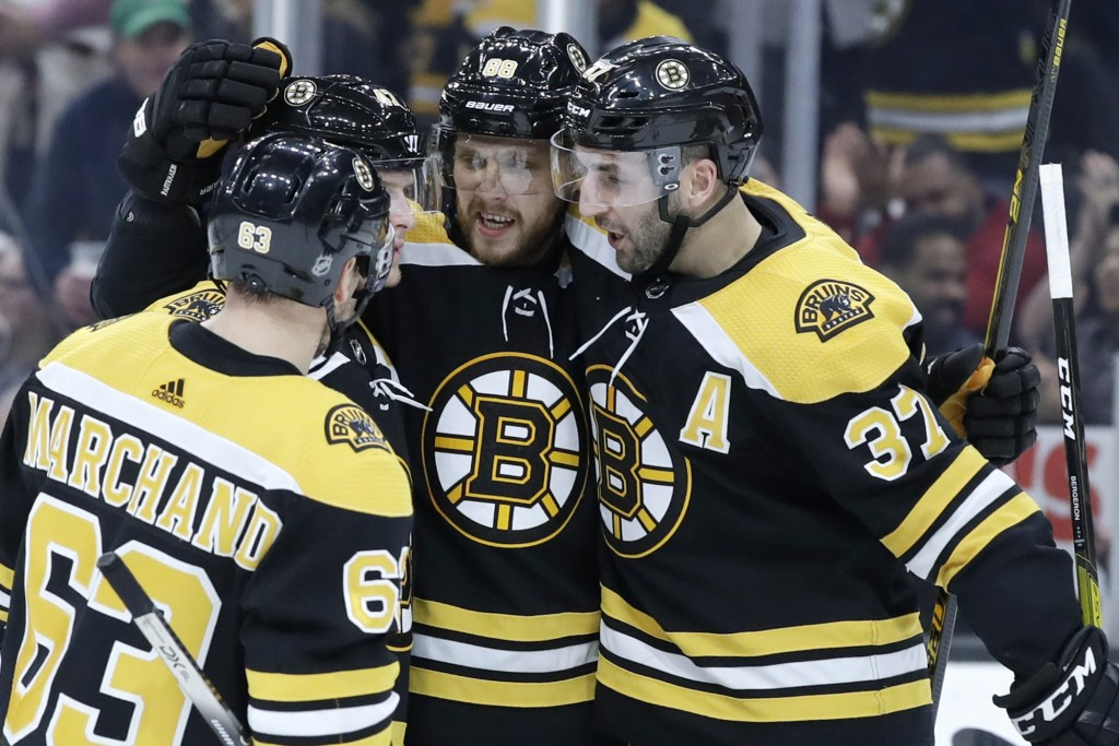 Boston Bruins right wing David Pastrnak celebrates his goal against the Columbus Blue Jackets with teammates Brad Marchand (63) and Patrice Bergeron (...