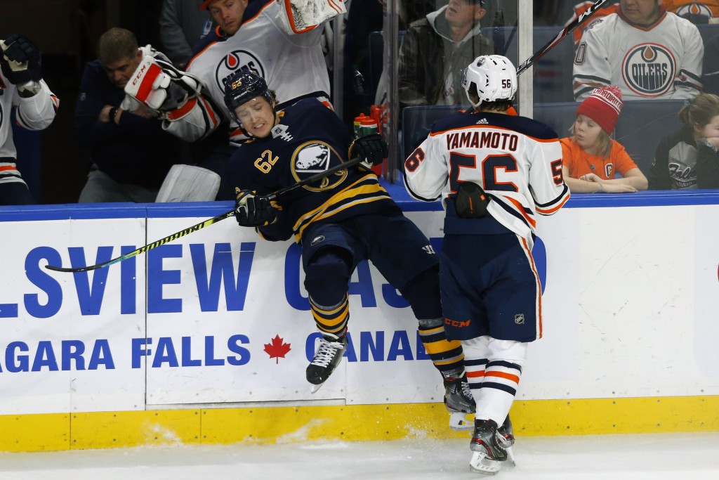 Buffalo Sabres defenseman Brandon Monyour (62) is checked by Edmonton Oilers forward Kailer Yamamoto (56) during the first period of an NHL hockey gam...