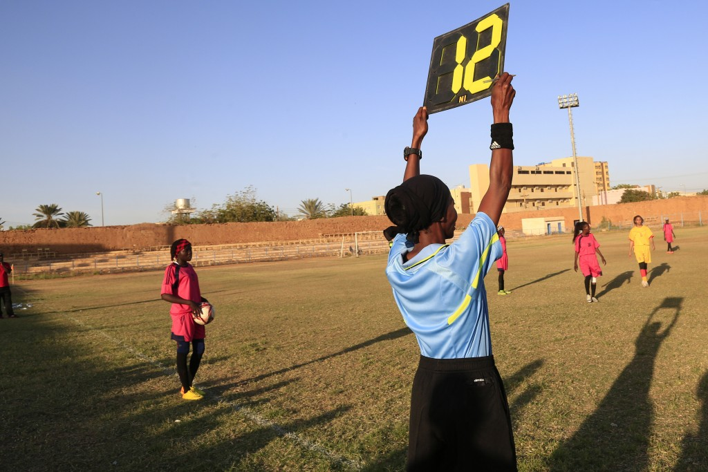 In this Wednesday, Dec. 11, 2019 photo, a referee holds a board as Sudanese al-Difaa, in pink, and al-Sumood women teams play in Omdurman, Khartoum's ...