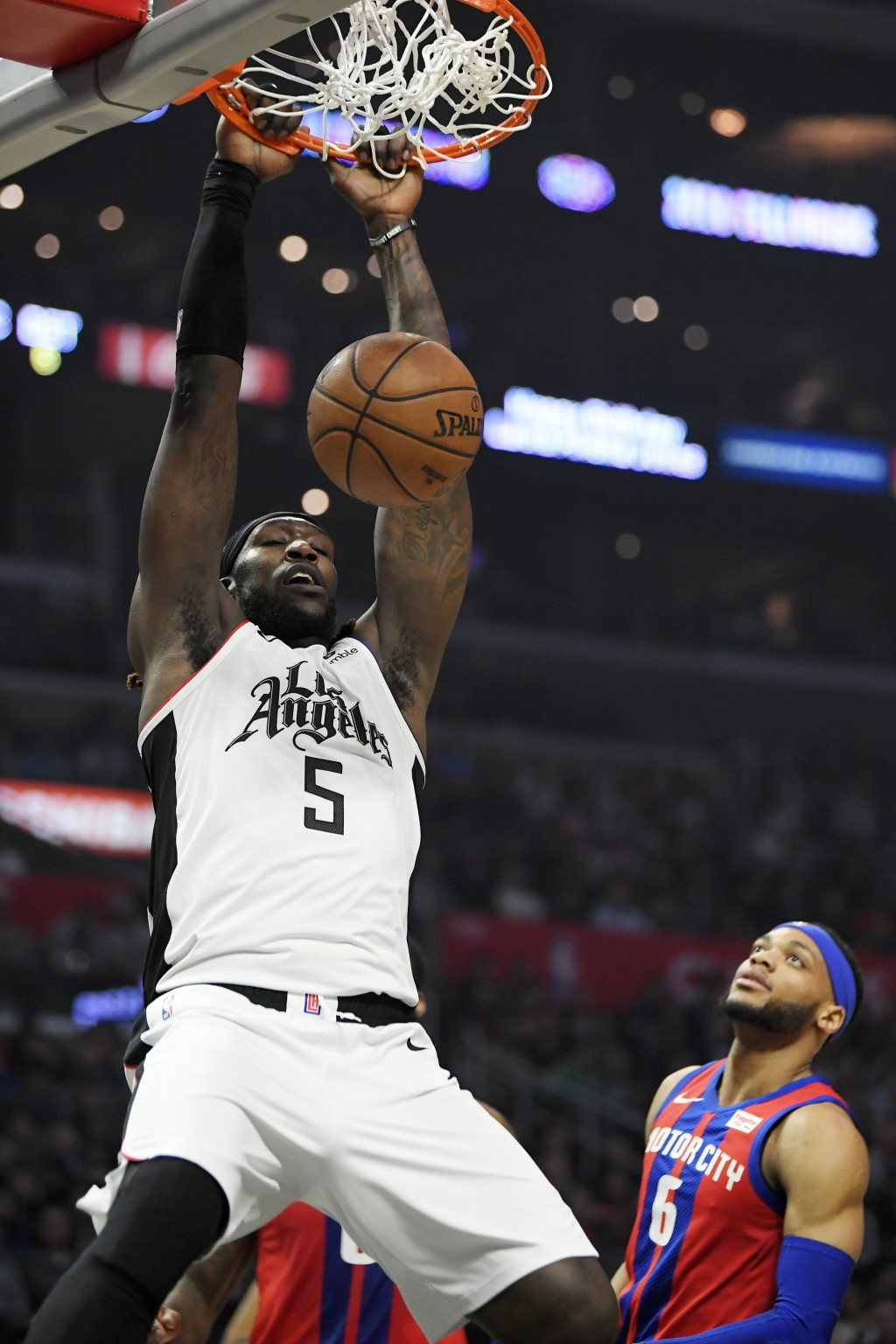 Los Angeles Clippers forward Montrezl Harrell dunks as Detroit Pistons guard Bruce Brown watches during the first half of an NBA basketball game Thurs...