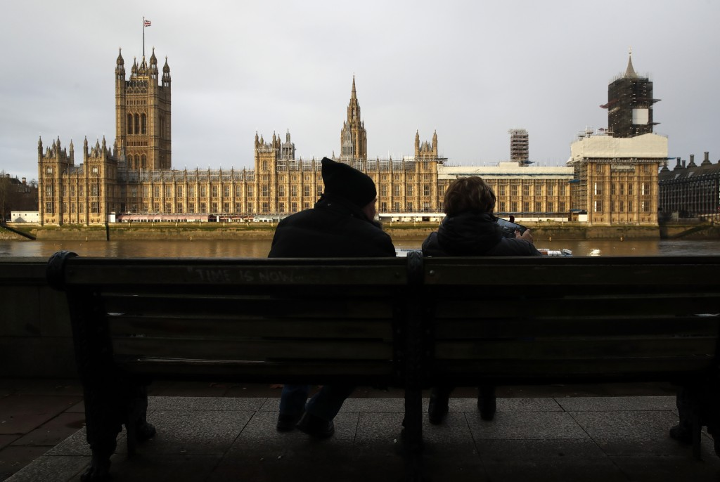 FILE - In this file photo dated Saturday, Dec. 14, 2019, a couple takes photos of Houses of Parliament in London. With a hefty government majority, ex...