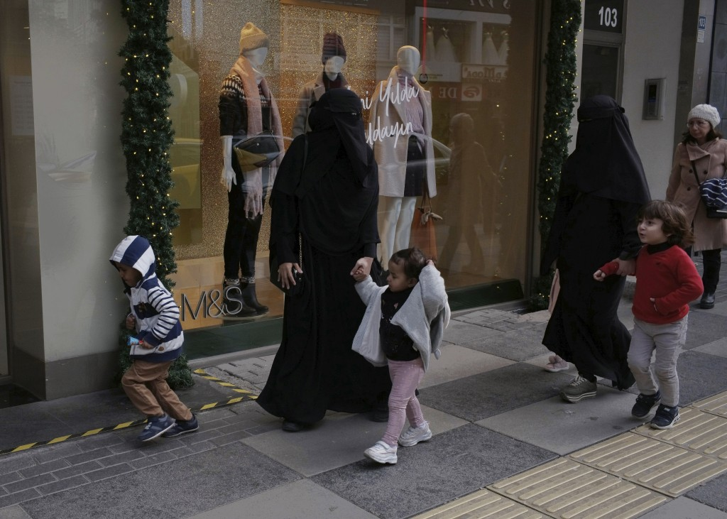 FILE - In this Dec. 3, 2019 file photo, refugee women walk with their children on a main street, in Ankara, Turkey.  Turkey currently host about four ...