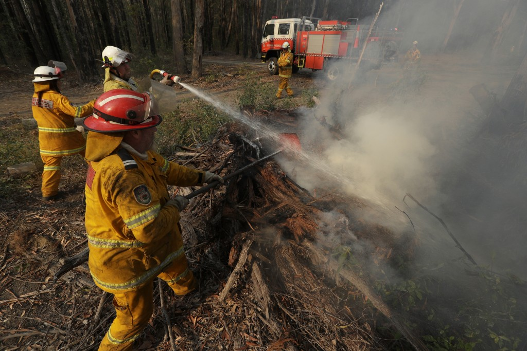 Firefighters battle a fire near Bendalong, Australia, Friday, Jan. 3, 2020. Navy ships plucked hundreds of people from beaches and tens of thousands w...