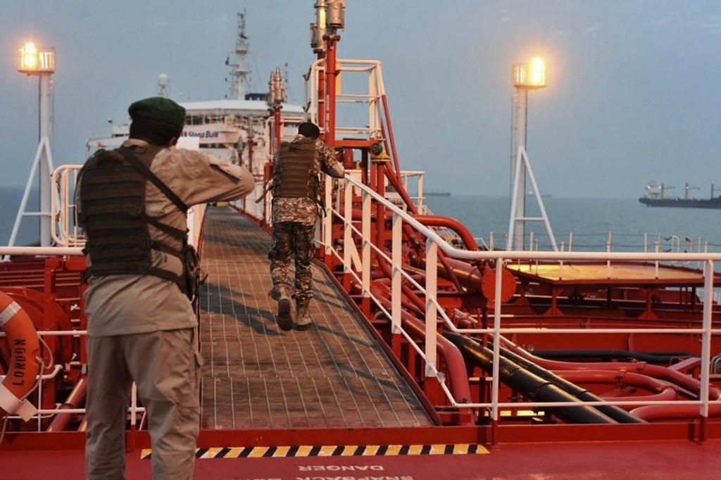 FILE - In this Sunday, July 21, 2019, photo, two armed members of Iran's Revolutionary Guard inspect the British-flagged oil tanker Stena Impero, whic...