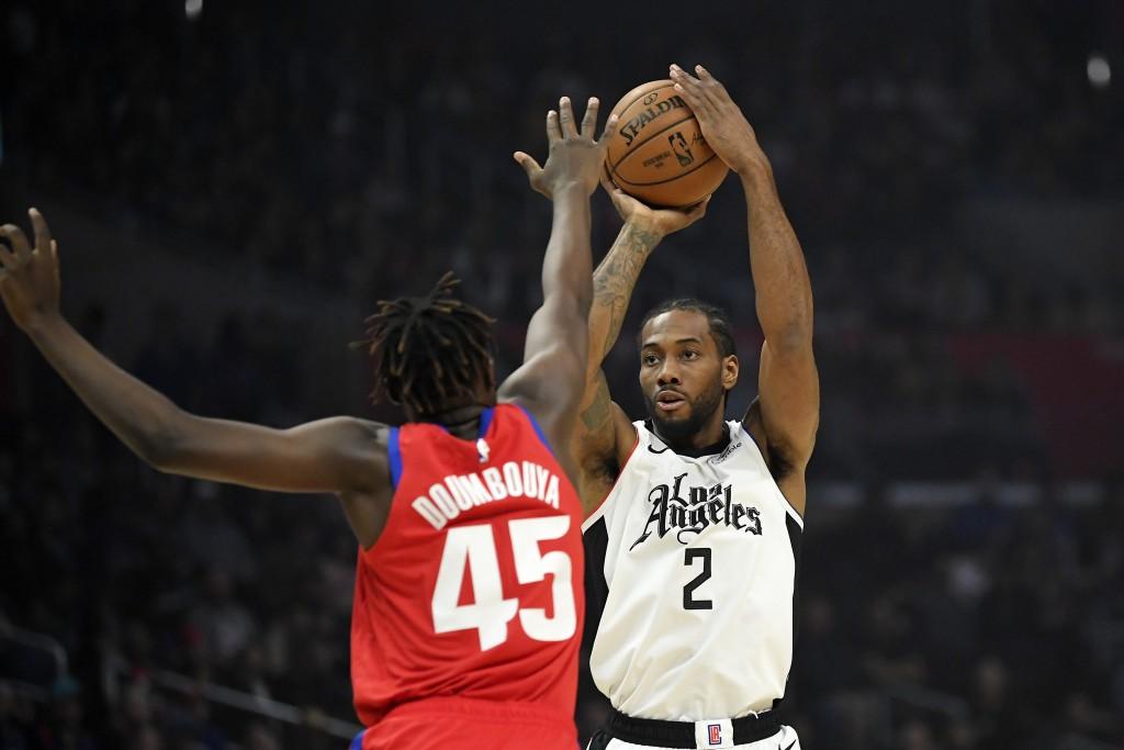 Los Angeles Clippers forward Kawhi Leonard, right, shoots as Detroit Pistons forward Sekou Doumbouya defends during the first half of an NBA basketbal...