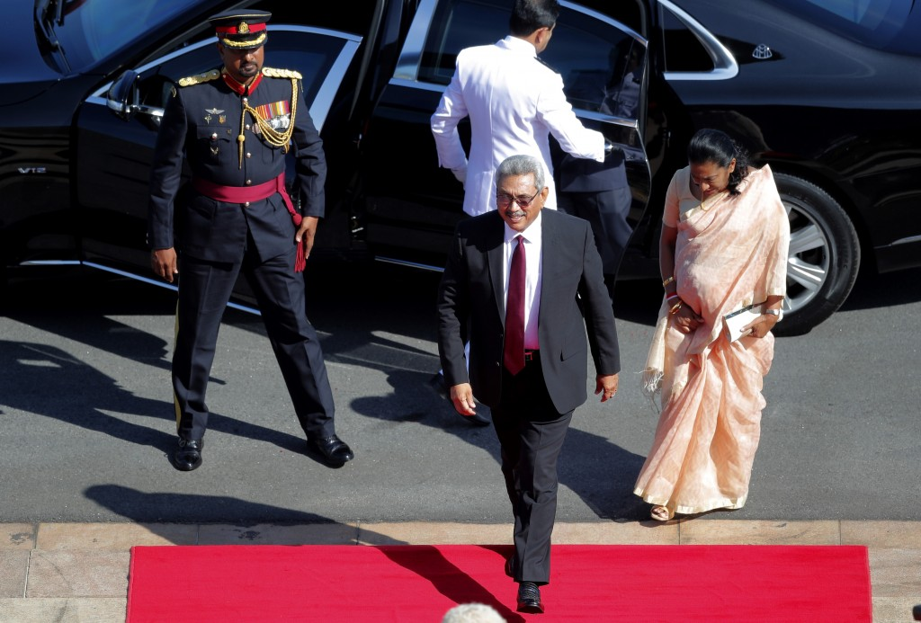 Sri Lankan President Gotabaya Rajapaksa, center, and the first lady Ayoma Rajapaksa, right, arrive at the parliament to address the ceremonial inaugur...
