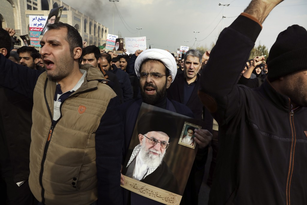 A cleric holds a poster of Iranian Supreme Leader Ayatollah Ali Khamenei and late revolutionary founder Ayatollah Khomeini, top right, while chanting ...