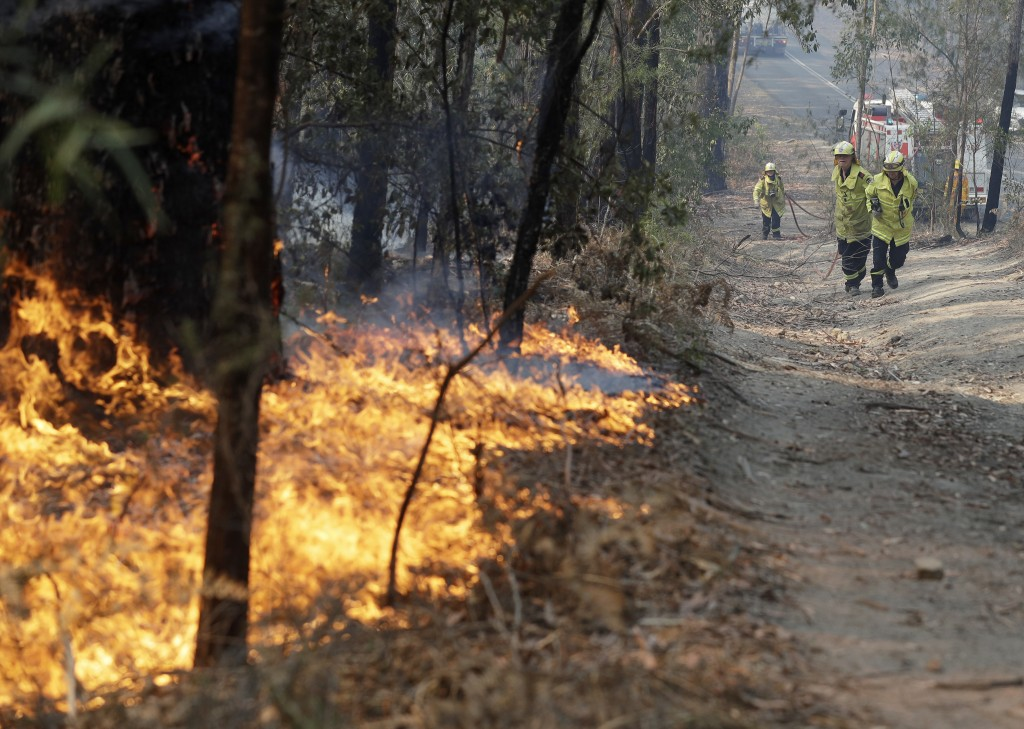 Firefighters drag a hose to battle a fire near Bendalong, Australia, Friday, Jan. 3, 2020. Navy ships plucked hundreds of people from beaches and tens...
