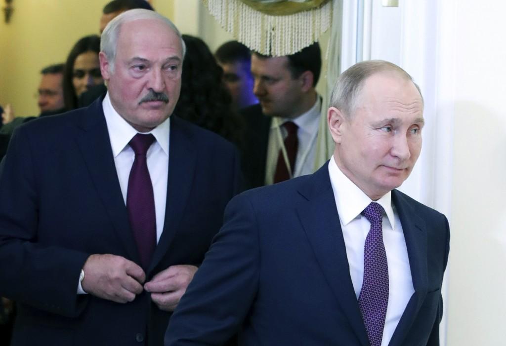 FILE - In this file photo taken on Friday, Dec. 20, 2019, Russian President Vladimir Putin, right, and Belarusian President Alexander Lukashenko walk ...