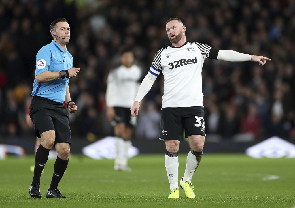 Derby County's Wayne Rooney talks with referee Dean Whitestone during the game against Barnsley, during their English Championship soccer match at Pri...