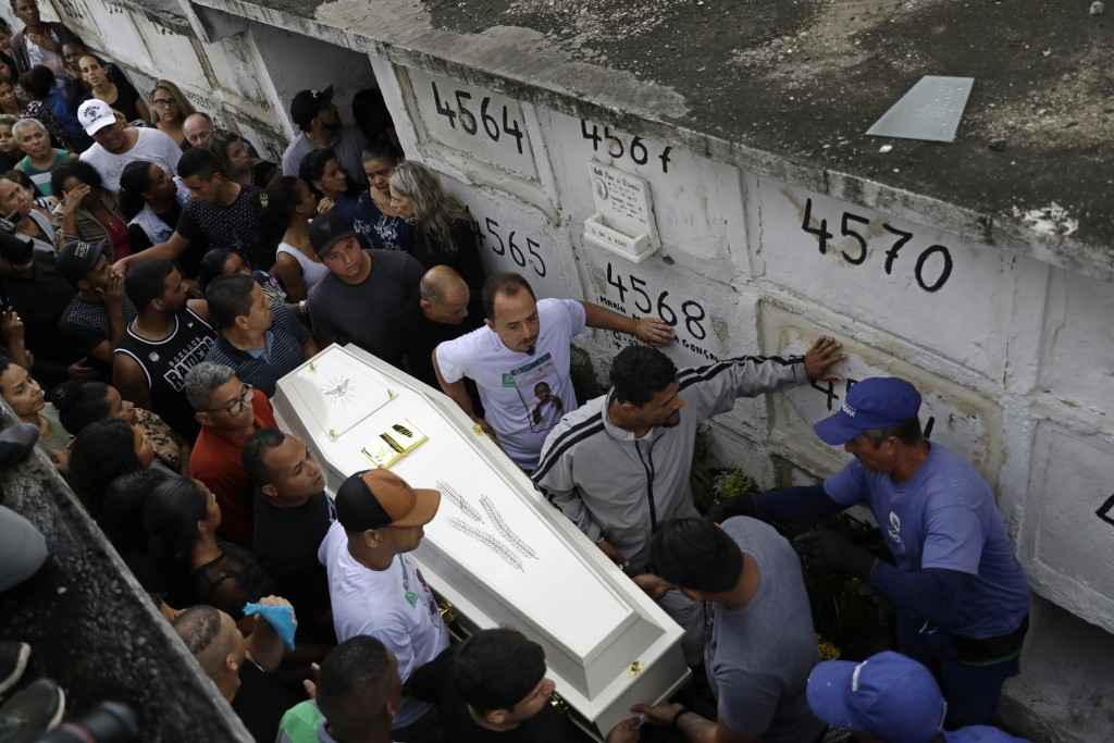FILE - In this Sept. 22, 2019 file photo, people carry the coffin of Agatha Sales Felix, who was hit by a a stray bullet, at a cemetery in Rio de Jane...
