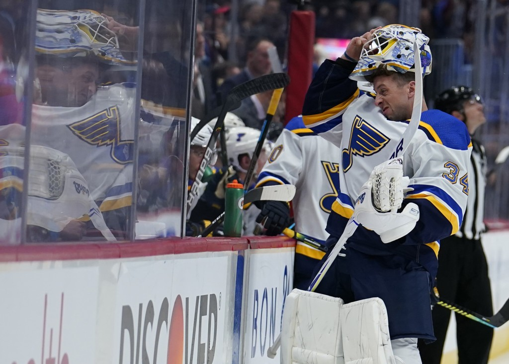 St. Louis Blues goaltender Jake Allen (34) puts on his mask to hit the ice and replace Jordan Binnington during the third period of the team's NHL hoc...