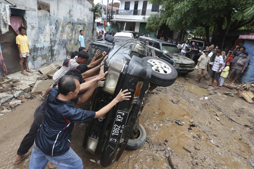 Residents move the wreckage of cars that were swept away by flood in Bekasi, West Java, Indonesia, Friday, Jan. 3, 2020. Severe flooding in greater Ja...