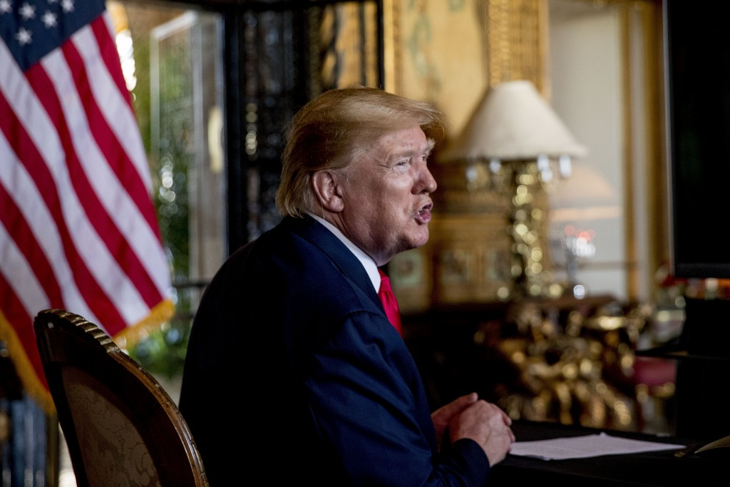 FILE - In this Dec. 24, 2019 photo, President Donald Trump speaks to members of the media following a Christmas Eve video teleconference with members ...