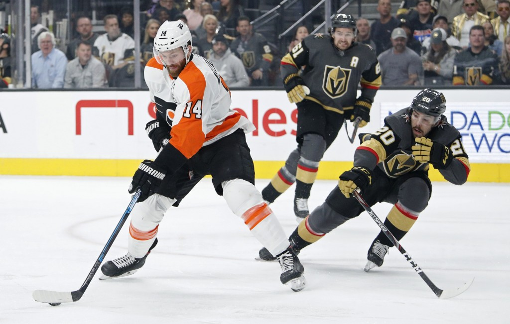 Philadelphia Flyers center Sean Couturier (14) skates around Vegas Golden Knights center Chandler Stephenson (20) during the first period of an NHL ho...