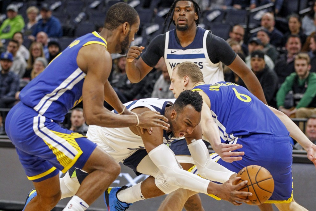 Minnesota Timberwolves guard Josh Okogie (20) drives between Golden State Warriors guard Alec Burks (8) and forward Alen Smailagic (6) and gets fouled...